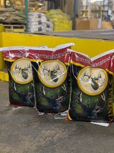Bags of Double Down Deer Feed Custom Minerals. They are yellow and red and green colored.